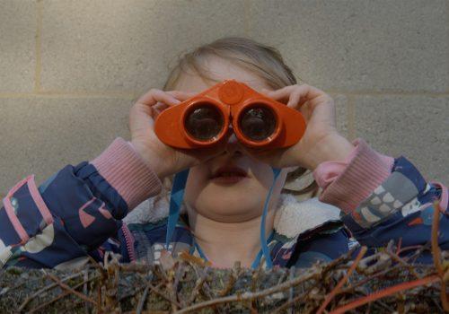 A young girl looks towards the camera using binoculars.