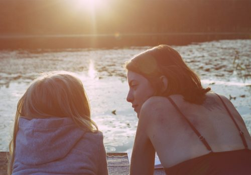 A woman and a young girl look out towards a lake at sunset.