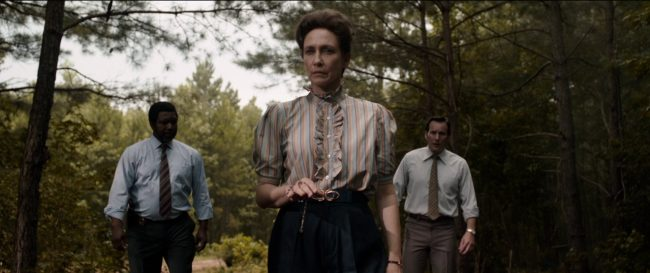 A woman, Lorraine Warren (Vera Farmiga) in 1980s-style dress, stands in a forest with two men either side of her. To the right is her husband, Ed Warren (Patrick Wilson).