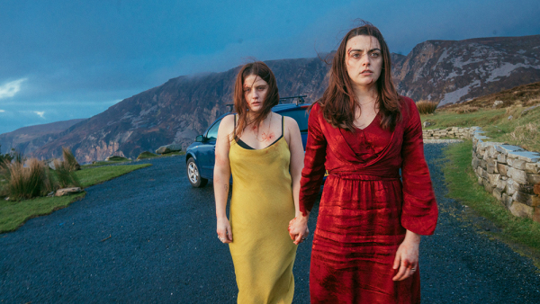 Two women with hints of blood on their clothes and faces hold hands in the centre of the image. They are walking away from a car parked on a rural road with rocky hills in the background.