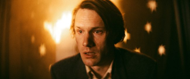 An exhausted man looks towards the ground, lit by the glow of a burning dollhouse.
